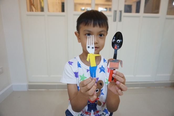 P.J was about to put on some hair on his spoon dolls.